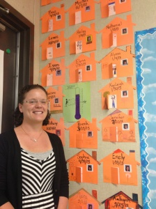 Stephanie Smith stands in front of a wall displaying documentation of her home visits.